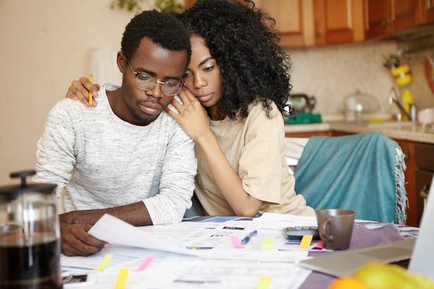 Gestresstes unglückliches junges afrikanisches ehepaar, das benachrichtigung von bank liest
