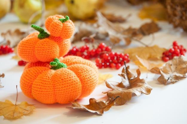 Gestrickte amigurumi kürbisse und fledermäuse an halloween