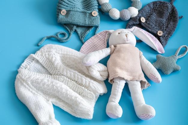 Gestrickte babykleidung und accessoires auf blau
