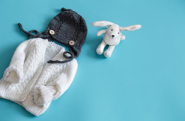 Gestrickte babykleidung und accessoires auf blauem grund.