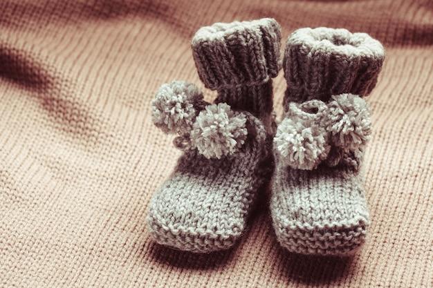 Gestrickte babyschuhe aus wolle mit pompons nahaufnahme