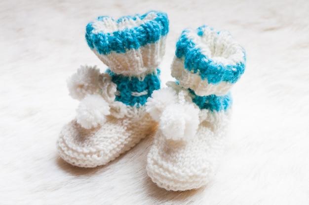 Gestrickte blaue babyschuhe für kleine jungen