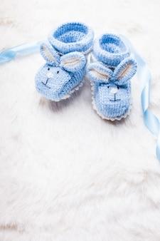 Gestrickte blaue babyschuhe mit kaninchenmaulkorb für kleine jungen