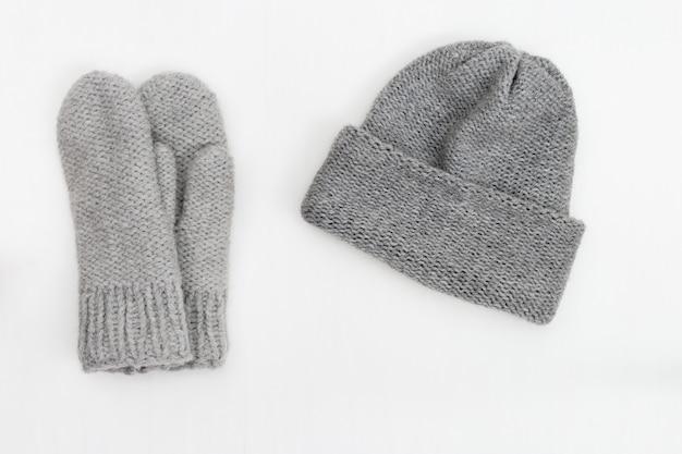 Gestrickte graue handschuhe und mütze. sicht von oben. kopieren sie platz.