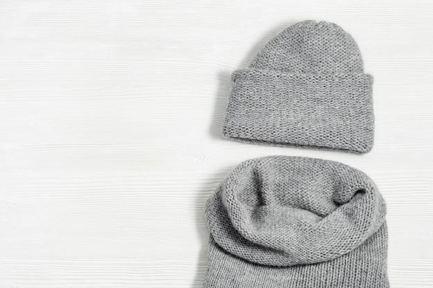 Gestrickte graue mütze und schal auf weißem hölzernem hintergrund. modische warme kleidung für mädchen oder frauen. flach liegen. ansicht von oben. kopieren sie platz.