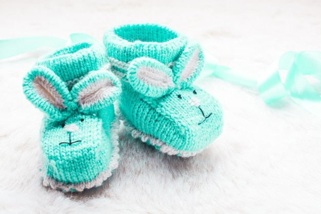 Gestrickte grüne babyschuhe mit kaninchenmaulkorb für kleine jungen