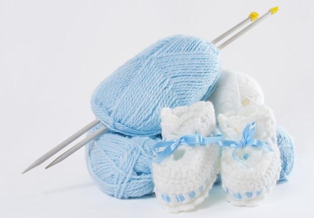 Gestrickte handgemachte babyschuhe, wollknäuel, nadeln