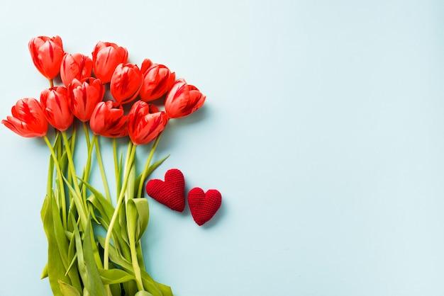 Gestrickte herzen in der nähe von tulpen