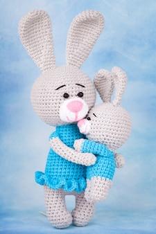 Gestrickte kaninchen - mutter und sohn mit geschenken und blumen.