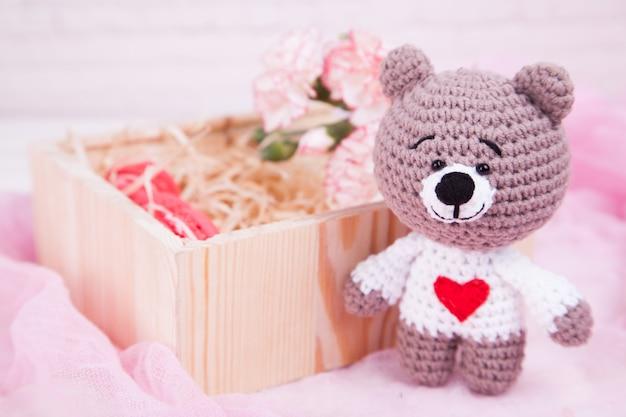 Gestrickte katze mit einem herzen und rosen. valentinstag dekor. gestricktes spielzeug, amigurumi.
