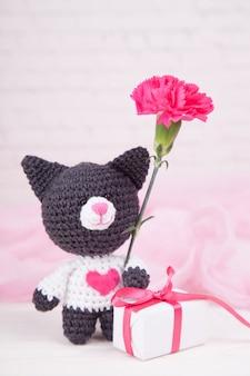Gestrickte katze mit herz. valentinstag dekor. gestricktes spielzeug, amigurumi. valentinstaggrußkarte.