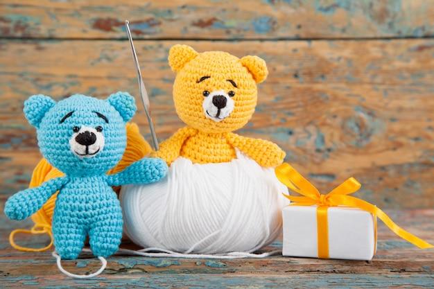 Gestrickte kleine bären auf einem alten hölzernen. handgemachtes, gestricktes spielzeug. amigurumi