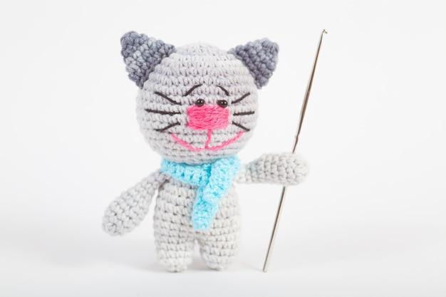 Gestrickte kleine katze auf einem weiß. handgemachtes, gestricktes spielzeug. amigurumi