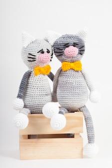 Gestrickte kleine katze auf einem weißen hintergrund. handgemachtes, gestricktes spielzeug. amigurumi