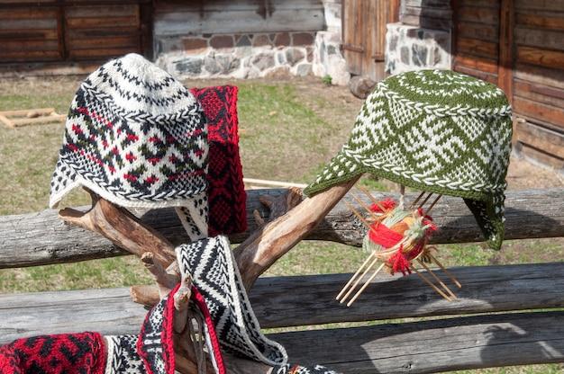 Gestrickte lettische mütze mit verzierung auf holzzaun draußen