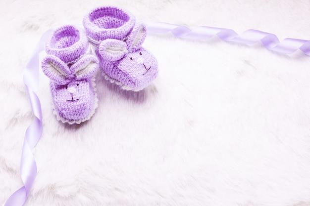 Gestrickte lila babyschuhe mit kaninchenmaulkorb über fell