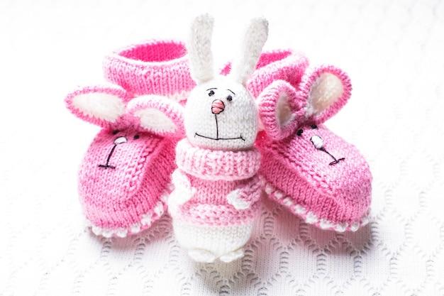 Gestrickte rosa babyschuhe mit hasenmaulkorb und spielzeug über textilhintergrund