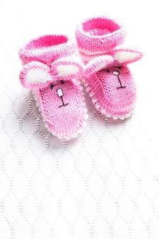 Gestrickte rosa babyschuhe mit kaninchenmaulkorb auf textilhintergrund