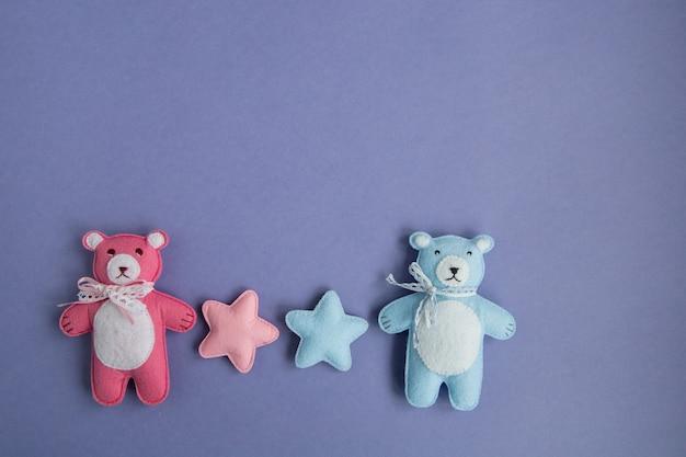Gestrickte spielzeuge wolke, stern, bär, widder, eule, vogelrosa und blaue farben liegen auf einem lila hintergrund