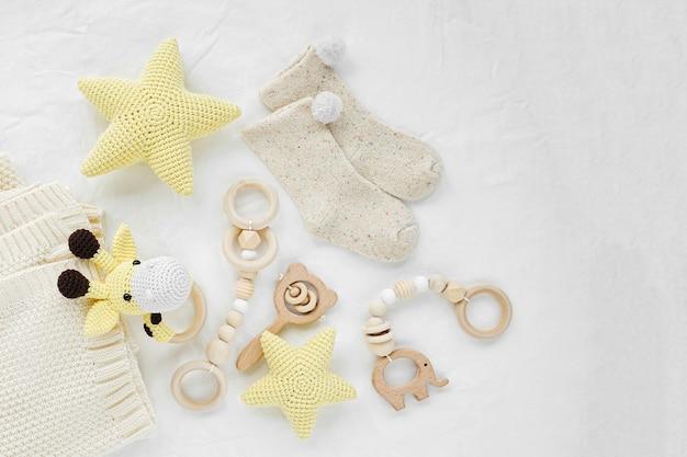 Gestrickte spielzeuggiraffe, gelbe sterne und hölzerner beißring für neugeborene auf weißem bett. geschlechtsneutrale babysachen und accessoires. flache lage, ansicht von oben