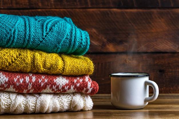 Gestrickte strickjacken und ein becher heißer kakao auf einem hölzernen hintergrund. winterkleidung. hässliche weihnachtsstrickjacke