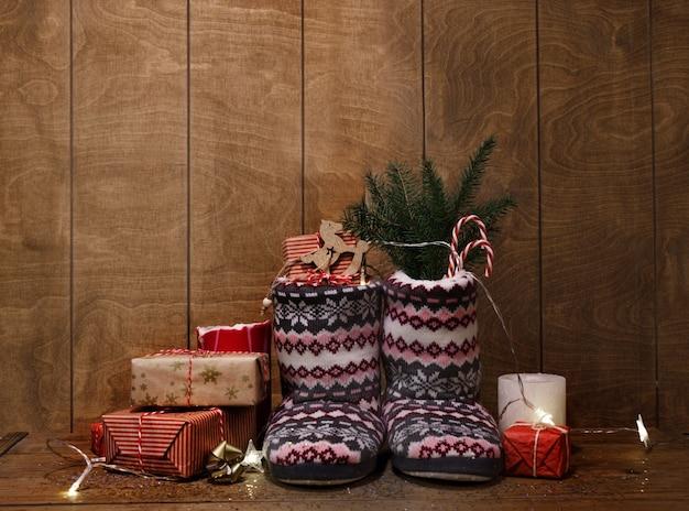 Gestrickte weihnachtsstiefel auf einem hölzernen hintergrund um geschenke