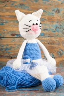 Gestrickte weiße katze in einem blauen kleid auf einem alten hölzernen hintergrund. handarbeit, kunsthandwerk. amigurumi