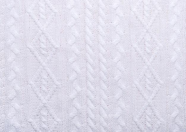 Gestrickte weiße textur mit muster aus verschiedenen zöpfen.