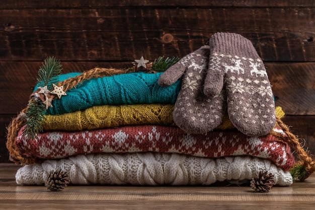 Gestrickte winterpullover und warme fäustlinge. winter- und herbstkleidung.
