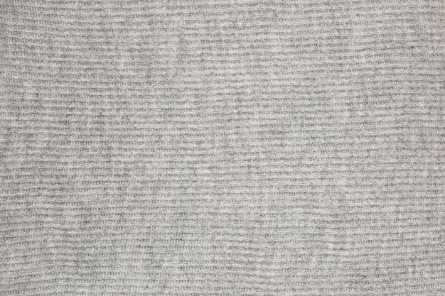 Gestrickte wolloberfläche mit grauer textur. hintergrund, tapete aus fasern. warmer stoff. hochwertiges foto