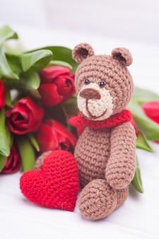 Gestrickter bär festliches dekor. zarte rote tulpen. valentinstag. handgemachtes, gestricktes spielzeug, amigurumi