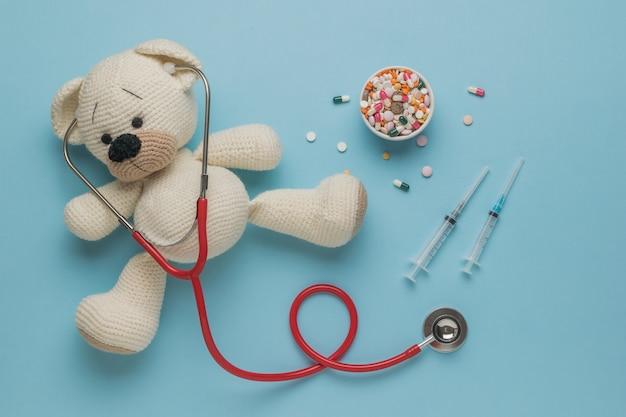 Gestrickter bär mit stethoskop, spritzen und pillen auf blauem hintergrund. das konzept der behandlung von krankheiten. flach liegen.