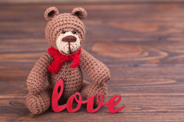 Gestrickter bär valentinstag dekor. gestricktes spielzeug, amigurumi. valentinstaggrußkarte.