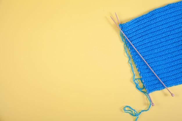 Gestrickter blauer schal liegt auf gelbem grund. handgemachtes konzept. speicherplatz kopieren.