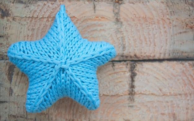 Gestrickter blauer stern auf hellem hölzernem hintergrund
