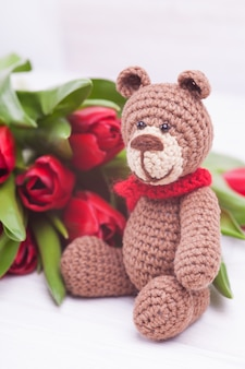 Gestrickter blumenstrauß des bären und der roten tulpen