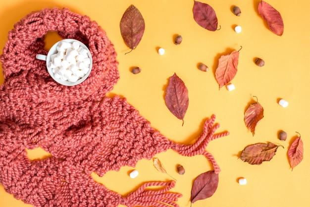 Gestrickter brauner schal, marshmallow, süßigkeiten, nüsse, goldene zapfen und zutaten für die herstellung von glühwein. heller trockener herbstlaub auf einem gelben hintergrund. gemütlicher herbst t. ansicht von oben. flach liegen.