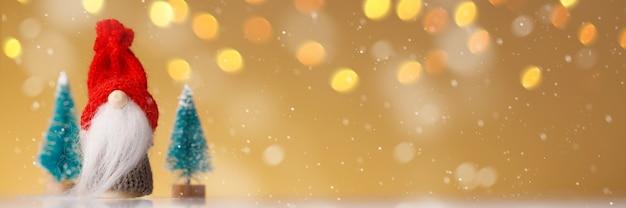 Gestrickter gnom mit baum auf goldhintergrund mit gelben lichtern und schneeflocken