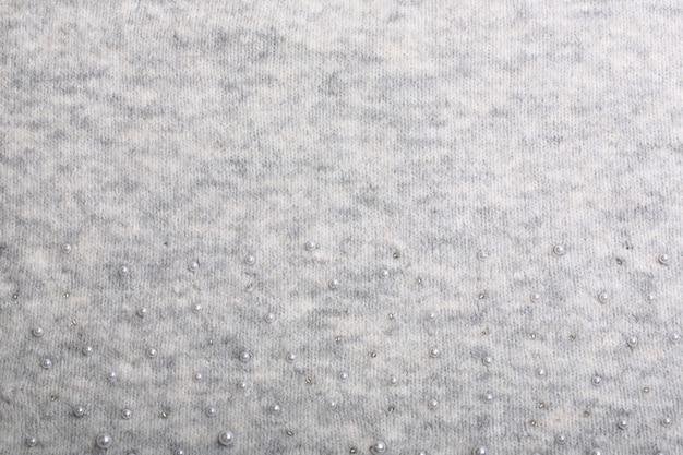 Gestrickter hintergrund. hellgraues sanftes wollhintergrundmuster. hintergrund mit perlen bestickt