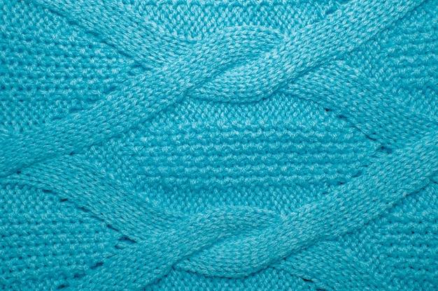 Gestrickter jersey-hintergrund mit reliefmuster. blaue wollpullover-textur nah oben