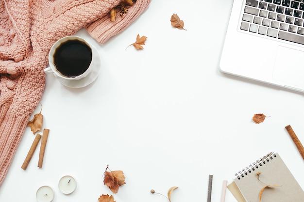 Gestrickter pullover, tasse kaffee, laptop, notizbuch, herbstlaub, zimtstangen, kerzen auf weißem hintergrund. herbstkomposition. home-office-schreibtisch arbeitsbereich. flache lage, draufsicht, kopierraum