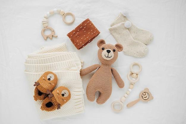 Gestrickter spielzeugbär, decke, socken und hölzerner beißring für neugeborene auf weißem bett. geschlechtsneutrale babysachen und accessoires. flache lage, ansicht von oben