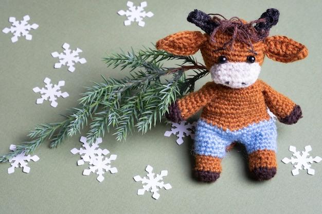 Gestrickter spielzeugbulle mit weihnachtsbaum und schneeflocken auf grünem hintergrund.