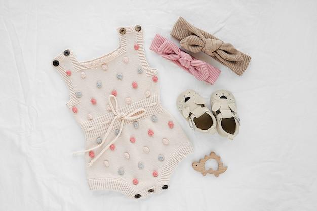 Gestrickter strampler und haarschleifen mit kinderschuhen für neugeborene auf weißer decke. babykleidung und accessoires. flache lage, ansicht von oben