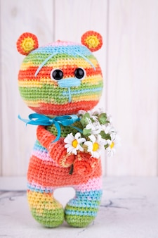 Gestrickter teddybär mit blumen. gestricktes spielzeug, handgemacht, amigurumi, kreativität, diy