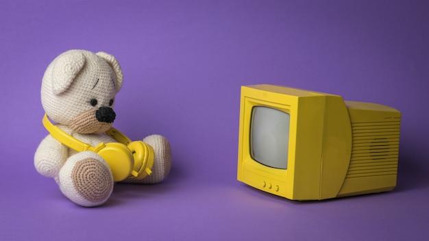 Gestrickter teddybär mit kopfhörern vor dem bildschirm.