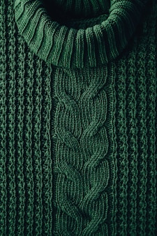 Gestrickter texturhintergrund eines wintergrünen hochhalspullovers