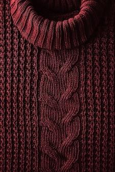 Gestrickter texturhintergrund eines winterroten pullovers mit hohem hals