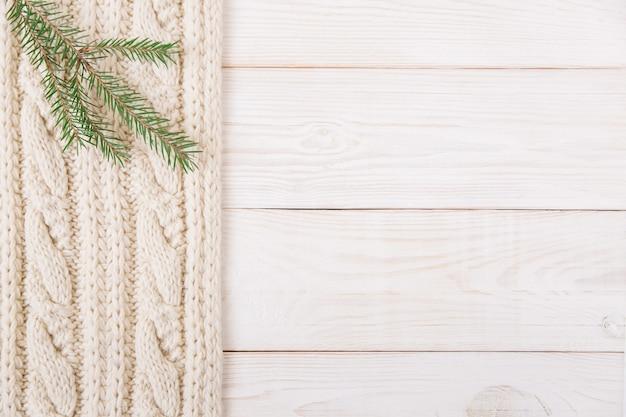 Gestrickter und hölzerner hintergrund mit weihnachtsbaumast. ansicht von oben. platz für text