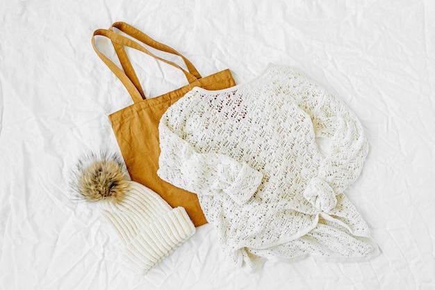 Gestrickter weißer pullover mit mütze und tragetasche. herbst-/wintermode-kleidungscollage auf weißem hintergrund. draufsicht flach.